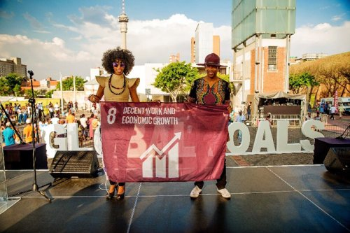 Singing duo Mafikizolo raised a flag to represent Goal 8, Decent Work and Economic Growth, at Constitution Hill in Johannesburg, South Africa, to support the UN Global Goals for Sustainable Development. Credit: Nicki Priem